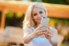 Mujer sonriente feliz que usa su teléfono en la ciudad Imagen de archivo libre de regalías