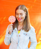 Mujer sonriente feliz soleada con la piruleta dulce del caramelo sobre fondo colorido Fotografía de archivo