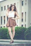 Mujer sonriente hermosa con el pelo rizado Mirada elegante urbana foto de archivo