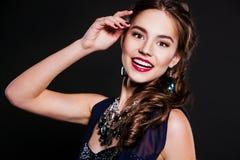 Mujer sonriente hermosa con joyería que lleva del maquillaje perfecto de la tarde Imagen de archivo libre de regalías