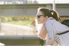 Mujer sonriente hermosa con las gafas de sol, inclinándose en el puente Fotografía de archivo