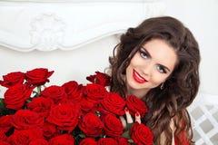 Mujer sonriente hermosa con maquillaje, ramo de las rosas rojas de la flor Fotografía de archivo libre de regalías