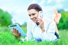 Mujer sonriente hermosa con PC de la tableta y el hablar en el teléfono móvil Foto de archivo libre de regalías
