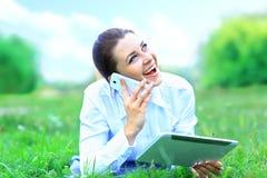 Mujer sonriente hermosa con PC de la tableta y el hablar en el teléfono móvil Fotos de archivo libres de regalías