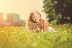 Mujer sonriente hermosa con PC de la tablilla, al aire libre Imagenes de archivo