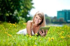 Mujer sonriente hermosa con PC de la tablilla, al aire libre Youn hermoso Fotografía de archivo