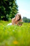 Mujer sonriente hermosa con PC de la tablilla, al aire libre Youn hermoso Fotos de archivo libres de regalías