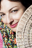 Mujer sonriente hermosa con una fan Imagen de archivo libre de regalías