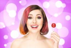 Mujer sonriente hermosa con una piruleta en fondo de la burbuja Foto de archivo