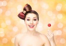 Mujer sonriente hermosa con una piruleta en fondo de la burbuja Imagen de archivo