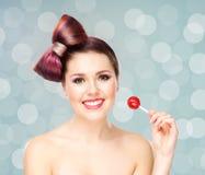 Mujer sonriente hermosa con una piruleta en fondo de la burbuja Fotografía de archivo