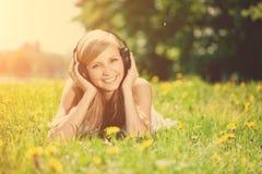 Mujer sonriente hermosa de la mujer que escucha la música en los auriculares o Fotografía de archivo libre de regalías