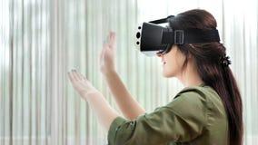 Mujer sonriente hermosa del ángulo bajo que goza jugando realidad aumentada en máscara de dispositivo de alta tecnología metrajes