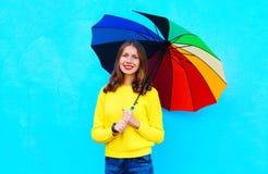 Mujer sonriente hermosa del retrato con el paraguas colorido en día del otoño sobre fondo azul colorido Imagen de archivo