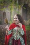 Mujer sonriente hermosa en vestido medieval largo con el espejo imagenes de archivo