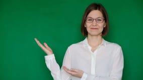Mujer sonriente hermosa en vidrios y la blusa blanca que señala a la derecha en la pantalla verde, llave de la croma almacen de metraje de vídeo