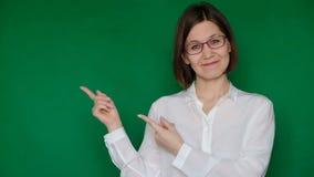 Mujer sonriente hermosa en vidrios y la blusa blanca que señala a la derecha en la pantalla verde, llave de la croma metrajes