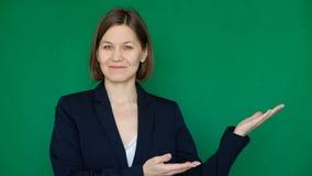 Mujer sonriente hermosa en vidrios y traje que señala a la derecha en la pantalla verde, llave de la croma Cierre para arriba almacen de video