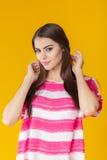 Mujer sonriente hermosa joven con el pelo largo en camisa rosada en fondo amarillo Fotos de archivo
