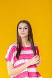 Mujer sonriente hermosa joven con el pelo largo en camisa rosada en fondo amarillo Foto de archivo