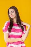 Mujer sonriente hermosa joven con el pelo largo en camisa rosada en fondo amarillo Foto de archivo libre de regalías