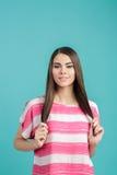 Mujer sonriente hermosa joven con el pelo largo en camisa rosada en fondo azul Foto de archivo libre de regalías