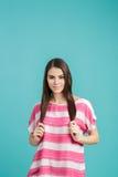 Mujer sonriente hermosa joven con el pelo largo en camisa rosada en fondo azul Fotografía de archivo