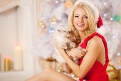 Mujer sonriente hermosa joven de santa cerca del árbol de navidad con Imagenes de archivo