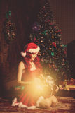 Mujer sonriente hermosa joven de santa cerca del árbol de navidad con Imagen de archivo
