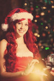 Mujer sonriente hermosa joven de santa cerca del árbol de navidad con Foto de archivo libre de regalías