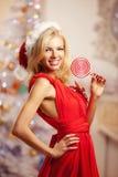 Mujer sonriente hermosa joven de santa cerca del árbol de navidad con Fotos de archivo libres de regalías