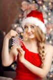 Mujer sonriente hermosa joven de santa cerca del árbol de navidad Fas Fotografía de archivo libre de regalías