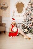Mujer sonriente hermosa joven de santa cerca del árbol de navidad Fas Imagen de archivo libre de regalías