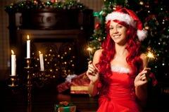 Mujer sonriente hermosa joven de santa cerca del árbol de navidad Gir Imágenes de archivo libres de regalías