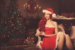 Mujer sonriente hermosa joven de santa cerca del árbol de navidad Gir Imagen de archivo