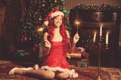 Mujer sonriente hermosa joven de santa cerca del árbol de navidad Gir Imagenes de archivo