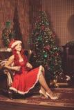 Mujer sonriente hermosa joven de santa cerca del árbol de navidad Gir Fotos de archivo libres de regalías