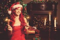 Mujer sonriente hermosa joven de santa cerca del árbol de navidad Gir Fotos de archivo