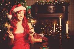 Mujer sonriente hermosa joven de santa cerca del árbol de navidad Gir Imagen de archivo libre de regalías