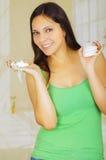 Mujer sonriente hermosa joven que lleva una blusa verde que sostiene el tapón del algodón de la menstruación con una mano y que s imagenes de archivo