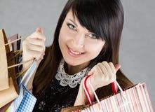 Mujer sonriente hermosa joven que sostiene las bolsas de papel foto de archivo libre de regalías