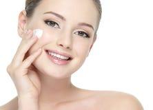 Mujer sonriente hermosa que aplica la crema en mejilla Imagen de archivo
