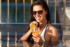 Mujer sonriente hermosa que bebe un cóctel en una piscina imágenes de archivo libres de regalías