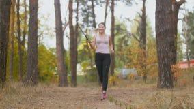 Mujer sonriente hermosa que hace el vídeo con el palillo del selfie de ella que corre en bosque almacen de metraje de vídeo