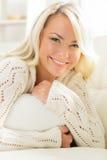 Mujer sonriente hermosa que pone en una almohada por la mañana imagen de archivo