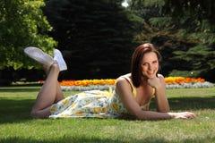 Mujer sonriente hermosa que se relaja en jardín del verano Imagen de archivo