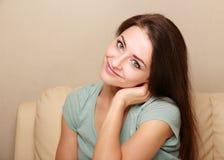 Mujer sonriente hermosa que se sienta en el sofá Foto de archivo