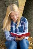 Mujer sonriente hermosa que se sienta en libro del parque y de lectura Imágenes de archivo libres de regalías