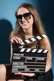 Mujer sonriente hermosa que sostiene una chapaleta de la película Imagenes de archivo