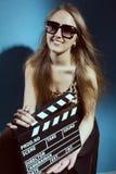 Mujer sonriente hermosa que sostiene una chapaleta de la película Imagen de archivo libre de regalías